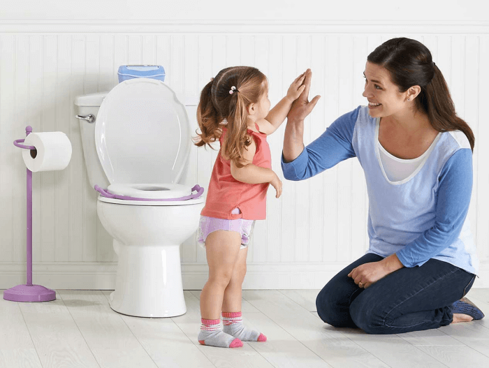 Photo of mother and young girl beside toilet fitted with child's potty training seat.