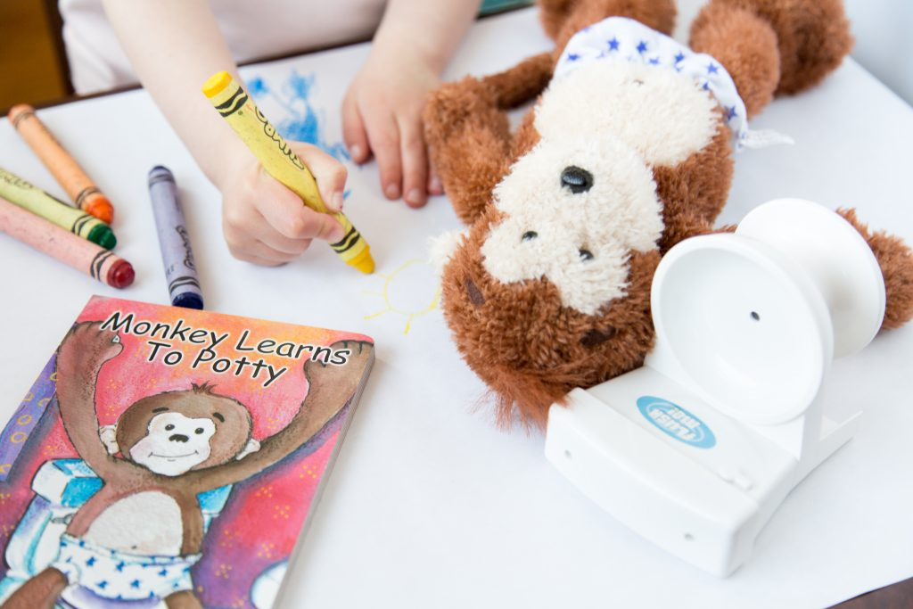Photo of young child coloring with Potty Monkey doll, toy potty, and Monkey Learns to Potty board book for potty training.