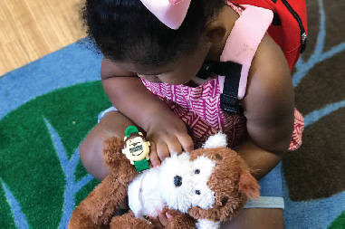 Young girl playing with Potty Monkey doll and Potty Monkey Watch