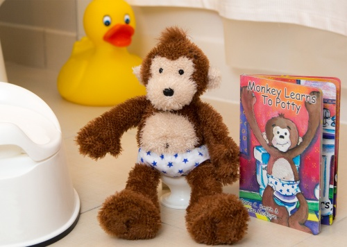 Potty Monkey sitting on his toilet, between a training potty seat and the Potty Monkey board book.