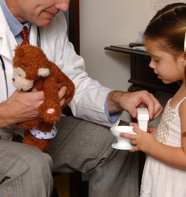 Doctor & child holding Potty Monkey and toy toilet.