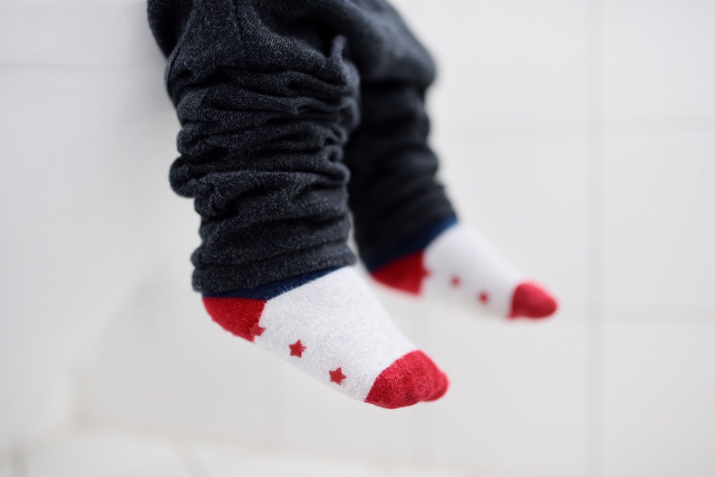 Toddler legs hanging in front of a toilet for potty training.